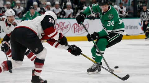 <p>               Arizona Coyotes defenseman Alex Goligoski (33) and Dallas Stars right wing Denis Gurianov (34) reach for the puck during the first period of an NHL hockey game in Dallas, Wednesday, Feb. 19, 2019. (AP Photo/Michael Ainsworth)             </p>