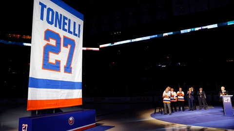 <p>               A banner with the name and number of former New York Islander Jon Tonelli is raised Friday, Feb. 21, 2020, in Uniondale, N.Y., as some of Tonelli's former teammates and an announcer, right applaud. (AP Photo/Kathy Willens)             </p>