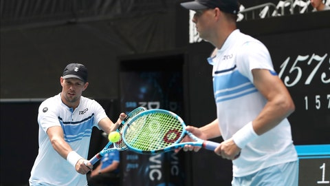 <p>               Mike Bryan, left, of the U.S. makes a backhand return as his brother Bob watches during their third round doubles match against Croatia's Ivan Dodig and Slovakia's Filip Polasek at the Australian Open tennis championship in Melbourne, Australia, Monday, Jan. 27, 2020. (AP Photo/Dita Alangkara)             </p>