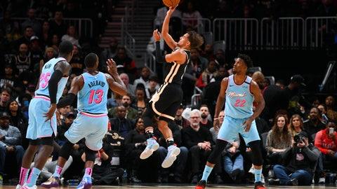 <p>               Atlanta Hawks guard Trae Young, second from right, shoots between Miami Heat forward Bam Adebayo (13) and forward Jimmy Butler (22) during the second half of an NBA basketball game Thursday, Feb. 20, 2020, in Atlanta. (AP Photo/John Amis)             </p>