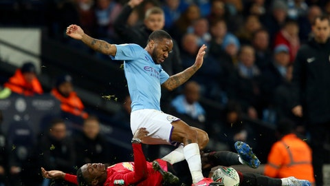 <p>               Manchester United's Aaron Wan-Bissaka, on the ground, tackles Manchester City's Raheem Sterling during the English League Cup semifinal second leg soccer match between Manchester City and Manchester United at Etihad stadium in Manchester, England, Wednesday, Jan. 29, 2020. (AP Photo/Dave Thompson)             </p>