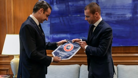 <p>               Greece's Prime Minister Kyriakos Mitsotakis, left, receives a gift from UEFA President Aleskander Ceferin, during their meeting in Athens, Tuesday, Feb. 25, 2020. Mitsotakis requested UEFA's help to clean up Greek soccer last month and has said he was willing to request expulsion of Greece's teams from European competition and even suspend the league unless major clubs sign up to a reform plan aimed stamping out match-related violence and widespread allegations of corruption in the sport. (AP Photo/Petros Giannakouris)             </p>