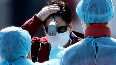 <p>               An official in protective suits measure the temperature of the foreign passengers disembarked from the quarantined Diamond Princess cruise ship before boarding to buses at a port in Yokohama, near Tokyo, Friday, Feb. 21, 2020. Japanese Prime Minister Shinzo Abe should be basking in the limelight this year in the runup to the 2020 Tokyo Olympics. Instead, the economy is reeling and criticism is mounting over his government's handling of a new virus that began in China and has spread alarmingly in Japan. (AP Photo/Eugene Hoshiko)             </p>