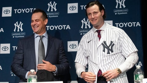 """<p>               FILE - In this Dec. 18, 2019, file photo, New York Yankees manager Aaron Boone, left, smiles as Gerrit Cole tries on a Yankee jersey as he is introduced in New York. The pitcher agreed to a 9-year $324 million contract. """"He's going to be a game changer for us,"""" Yankees owner Hal Steinbrenner said. """"The city's buzzing, and it's continued since the day we signed him."""" (AP Photo/Mark Lennihan, File)             </p>"""