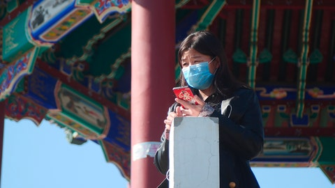 <p>               A woman wearing a face mask stands at a pagoda in Ritan Park in Beijing, Tuesday, Feb. 18, 2020. A hospital director who helped lead the fight against China's new virus has become one of its victims. His death comes as authorities are cautiously cheering a reduction in the number of new daily cases and deaths, along with the results of a study showing most people who contract the virus experience only mild symptoms. (AP Photo/Sam McNeil)             </p>