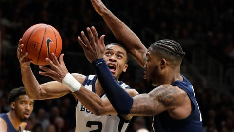 Butler guard Aaron Thompson (2) shoots under pressure from Xavier forward Tyrique Jones (4) in the first half of an NCAA college basketball game in Indianapolis, Wednesday, Feb. 12, 2020. (AP Photo/Michael Conroy)