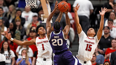 Kansas State's Xavier Sneed (20) tries to shoot the ball over Texas Tech's Terrence Shannon Jr. (1) and Kevin McCullar (15) during the second half of an NCAA college basketball game Wednesday, Feb. 19, 2020, in Lubbock, Texas. (Brad Tollefson/Lubbock Avalanche-Journal via AP)