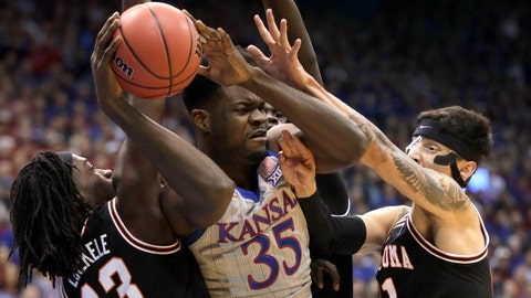 Kansas center Udoka Azubuike (35) rebounds between Oklahoma State guards Isaac Likekele (13) and Lindy Waters III (21) during the first half of an NCAA college basketball game in Lawrence, Kan., Monday, Feb. 24, 2020. (AP Photo/Orlin Wagner)