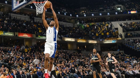 Indiana Pacers forward T.J. Warren dunks in front of Milwaukee Bucks defenders Khris Middleton, center, and Ersan Ilyasova during the first half of an NBA basketball game in Indianapolis, Wednesday, Feb. 12, 2020. (AP Photo/AJ Mast)