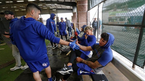 <p>               Texas Rangers minor league players Chris Seise, right, and Kevin Mendoza shake hands in greeting in the batting cages Thursday, March 12, 2020, in Surprise, Ariz. Major League Baseball is delaying the start of its season by at least two weeks because of the coronavirus outbreak and has suspended the rest of its spring training game schedule. (AP Photo/Elaine Thompson)             </p>