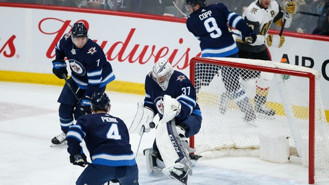 <p>               Winnipeg Jets goaltender Connor Hellebuyck (37) makes a save as Dmitry Kulikov (7) and Neal Pionk (4) defend against the Vegas Golden Knights during the first period of an NHL hockey game Friday, March 6, 2020, in Winnipeg, Manitoba. (John Woods/The Canadian Press via AP)             </p>