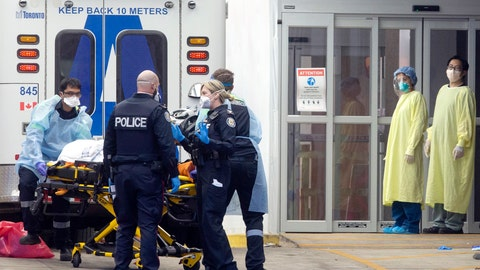 <p>               Hospital staff dressed in protective equipment stand by as a patient is taken out of an ambulance at Toronto's Mount Sinai Hospital, Sunday, March 29, 2020. The new coronavirus causes mild or moderate symptoms for most people, but for some, especially older adults and people with existing health problems, it can cause more severe illness or death. (Chris Young/The Canadian Press via AP)             </p>