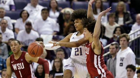<p>               Washington's RaeQuan Battle (21) passes the ball as Washington State's Jervae Robinson (1) and CJ Elleby defend during the second half of an NCAA college basketball game Friday, Feb. 28, 2020, in Seattle. Washington State won 78-74. (AP Photo/Elaine Thompson)             </p>
