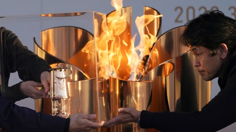 "<p>               Officials light a lantern from the Olympic Flame at the end of a flame display ceremony in Iwaki, northern Japan, Wednesday, March 25, 2020. IOC President Thomas Bach has agreed ""100%"" to a proposal of postponing the Tokyo Olympics for about one year until 2021 because of the coronavirus outbreak. (AP Photo/Eugene Hoshiko)             </p>"