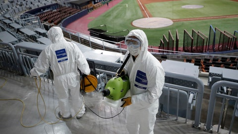 <p>               Workers wearing protective gears disinfect as a precaution against the new coronavirus at Gocheok Sky Dome in Seoul, South Korea, Tuesday, March 17, 2020. The Korea Baseball Organization has postponed the start of new season to prevent the spread of the new coronavirus. For most people, the new coronavirus causes only mild or moderate symptoms. For some it can cause more severe illness. (AP Photo/Lee Jin-man)             </p>
