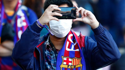 <p>               A Barcelona fan wears a face mask in an attempt to protect there self from the coronavirus uses his mobile prior a Spanish La Liga soccer match between Barcelona and Real Sociedad at the Camp Nou stadium in Barcelona, Spain, Saturday, March 7, 2020. (AP Photo/Joan Monfort)             </p>
