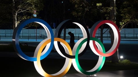 "<p>               A man is seen through the Olympic rings in front of the New National Stadium in Tokyo, Tuesday, March 24, 2020. IOC President Thomas Bach has agreed ""100%"" to a proposal of postponing the Tokyo Olympics for about one year until 2021 because of the coronavirus outbreak, Japanese Prime Minister Shinzo Abe said Tuesday. (AP Photo/Jae C. Hong)             </p>"
