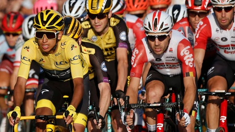 <p>               FILE - In this Sunday, July 28, 2019 file photo, Colombia's Egan Bernal, left, wearing the overall leader's yellow jersey, center, races on the Champs Elysees during the Tour de France cycling race in Paris. The team of reigning Tour de France champion Egan Bernal has withdrawn from all races over the next three weeks amid the spread of the new virus outbreak and following the death of one of its sports directors. (AP Photo/Michel Euler, File)             </p>