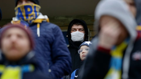 <p>               In this photo taken on Thursday, March 19, 2020, football fans of FC Bate, one of them wearing a face mask, watch the Belarus Championship soccer match between Energetik-BGU and Bate in Minsk, Belarus. Longtime Belarus President Alexander Lukashenko is proudly keeping soccer and hockey arenas open even though most sports around the world have shut down because of the coronavirus pandemic. The new coronavirus causes mild or moderate symptoms for most people, but for some, especially older adults and people with existing health problems, it can cause more severe illness or death. (AP Photo/Sergei Grits)             </p>
