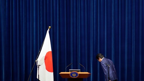 """<p>               FILE - In this March 14, 2020, file photo, Japanese Prime Minister Shinzo Abe bows to toward a Japanese flag before delivering his speech at the Prime Minister's office in Tokyo. Prime Minister Abe might be the biggest loser if the Tokyo Olympics don't go off as planned in just over four months. Abe has attached himself to the success of the Olympics since pushing hard for Tokyo's selection at an IOC meeting in 2013 in Buenos Aires, Argentina. Tokyo was picked over Istanbul by billing itself as a """"safe pair of hands.""""  (AP Photo/Eugene Hoshiko, File)             </p>"""