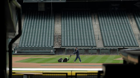 <p>               A grounds crew worker cuts the infield in front of empty seats at T-Mobile Park in Seattle, Thursday, March 26, 2020, around the time when the first pitch would have been thrown in the Mariners' Opening Day baseball game against the visiting Texas Rangers. Earlier in the month, Major League Baseball called off the start of the season due to the outbreak of the new coronavirus. (AP Photo/Ted S. Warren)             </p>