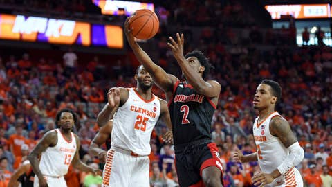 <p>               Louisville's Darius Perry (2) drives to the basket while defended by Clemson's Aamir Simms, left, and Al-Amir Dawes during the first half of an NCAA college basketball game Saturday, Feb. 15, 2020, in Clemson, S.C. (AP Photo/Richard Shiro)             </p>