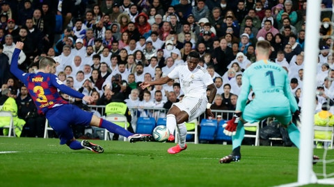 <p>               Real Madrid's Vinicius Junior, center, scores his side's opening goal past Barcelona's goalkeeper Marc-Andre ter Stegen, right, as Barcelona's Gerard Pique tries to block during the Spanish La Liga soccer match between Real Madrid and Barcelona at the Santiago Bernabeu stadium in Madrid, Spain, Sunday, March 1, 2020. (AP Photo/Manu Fernandez)             </p>