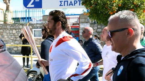 "<p>               US actor Gerard Butler runs as a torchbearer during the Olympic torch relay of the 2020 Tokyo Olympic Games in the southern Greek town of Sparta, Friday, March 13, 2020. Greece's Olympic committee says it is suspending the rest of its torch relay for the Olympic flame due to the ""unexpectedly large crowd"" that gathered to watch despite repeated requests for the public to stay away to prevent the spread of the new coronavirus. (AP Photo)             </p>"