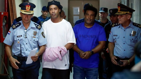<p>               Former soccer star Ronaldinho, second from left, and his brother Roberto de Assis Moreira walks escorted by police officers to declare to judge Clara Ruiz Diaz at Justice Palace in Asuncion, Paraguay, Saturday, March 7, 2020. Ronaldinho and his brother Roberto were alleged to enter to the country with a false Paraguayan passport.(AP Photo/Jorge Saenz)             </p>
