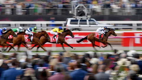 <p>               FILE - In this Nov. 7, 2017, file photo, horse race past the crowd during race 1 before the running of the Melbourne Cup at Flemington Racecourse in Melbourne. In Australia, where horse racing is arguably more popular than in any other country on the planet, the sport is continuing, minus the spectators, despite the nation's struggle to contain the new coronavirus. (AP Photo/Andy Brownbill, File)             </p>