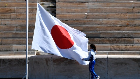<p>               An athlete adjusts the Japanese flag during the Olympic flame handover ceremony for the 2020 Tokyo Summer Olympics, in Athens, Thursday, March 19, 2020. The ceremony was held behind closed doors and with the presence of few members of the media because of fears over the new coronavirus. (Aris Messinis/Pool via AP)             </p>
