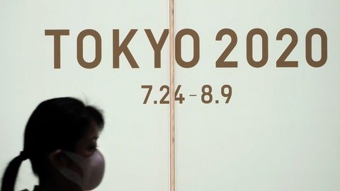 <p>               A woman walks past a large display promoting the Tokyo 2020 Olympics in Tokyo, Friday, March 13, 2020. U.S. President Donald Trump's suggestion to postpone the Tokyo Olympics for a year because of the spreading coronavirus was immediately shot down by Japan's Olympic minister. For most people, the new coronavirus causes only mild or moderate symptoms. For some it can cause more severe illness. (AP Photo/Jae C. Hong)             </p>
