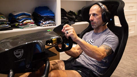 <p>               IndyCar driver Tony Kanaan, of Brazil, practices on his racing simulator in his home in Indianapolis, Saturday, March 28, 2020. Kanaan, along with other IndyCar drivers and NASCAR's Jimmie Johnson will compete in the series' inaugural virtual racing event Saturday. (AP Photo/Michael Conroy)             </p>