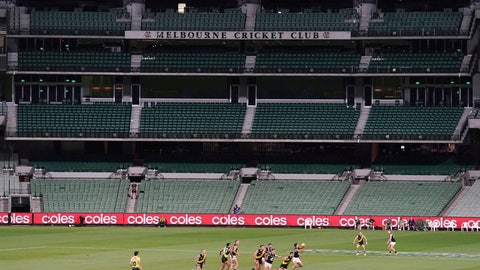 <p>               Players from Richmond and Carlton play their Australian Rules Football league game at a empty Melbourne Cricket Ground in Melbourne, Thursday, March 19, 2020, after bans on crowds of more than 500 assembling at outdoor venues amid the coronavirus pandemic. At the MCG less than two weeks ago, more than 86,000 people gathered to watch Australia beat India in the women's Twenty20 Cricket World Cup final. Sports are, evidently, a major part of life in Melbourne, where Aussie rules was invented. (Michael Dodge/AAP Image via AP)             </p>