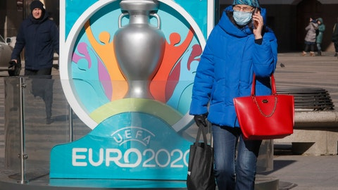 <p>               A woman wears a medical mask walks past a sign with Euro 2020 emblem in St.Petersburg where UEFA planned to host four UEFA EURO 2020 matches, including a quarter final, in Russia, Tuesday, March 17, 2020. UEFA today announced the postponement of its flagship national team competition, UEFA EURO 2020, due to be played in June and July this year, avoiding placing any unnecessary pressure on national public services involved in staging matches. For some people the new COVID-19 coronavirus causes only mild or moderate symptoms, but for some it can cause more severe illness. (AP Photo/Dmitri Lovetsky)             </p>