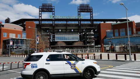 <p>               FILE - In this March 24, 2020, file photo, a Police vehicle blocks a street near Citizens Bank Park, home of the Philadelphia Phillies baseball team, in Philadelphia. On MLB's opening day, ballparks will be empty with the start of the season on hold because of the coronavirus pandemic. (AP Photo/Matt Slocum, File)             </p>