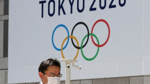 <p>               FILE - In this Wednesday, March 25, 2020, file photo, a man walks in front of a Tokyo Olympics logo at the Tokyo metropolitan government headquarters. The postponement of the Tokyo Games has catapulted the sports organizations that make up the backbone of the U.S. Olympic team into crisis. (AP Photo/Koji Sasahara, File)             </p>