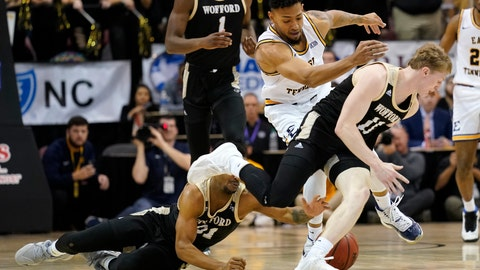 <p>               Wofford guard Tray Hollowell (21), East Tennessee State forward Jeromy Rodriguez (11) and Wofford guard Trevor Stumpe (15) scramble for the ball during the first half of an NCAA men's college basketball championship game for the Southern Conference tournament, Monday, March 9, 2020, in Asheville, N.C. (AP Photo/Kathy Kmonicek)             </p>