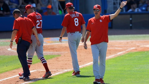 St. Louis Cardinals pitching coach Mike Maddux , right, motions toward the bullpen as manager Mike Shildt (8) and a trainer walk with pitcher Brett Cecil (2) after he suffered an apparent injury while covering first base on a ground ball by New York Mets' Jeff McNeil during the sixth inning of a spring training baseball game, Wednesday, March 11, 2020, in Port S. Lucie, Fla. (AP Photo/Julio Cortez)