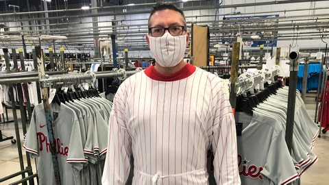 This image provided by Fanatics shows a model wearing a protective mask and gown for medical professionals made from the fabric of a baseball uniform. Fanatics, the company that manufactures uniforms for Major League Baseball in Pennsylvania, has suspended production on jerseys and is instead using the polyester mesh fabric to make masks and gowns that help fill the dearth of protective wear at hospitals in Pennsylvania and nearby states. (Fanatics via AP)