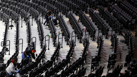 Workers clean the Wells Fargo Center after an NBA basketball game between the Philadelphia 76ers and the Detroit Pistons, Wednesday, March 11, 2020, in Philadelphia. (AP Photo/Matt Slocum)
