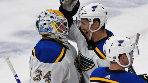 St. Louis Blues goaltender Jake Allen (34) and Tyler Bozak (21), right, celebrate against the Chicago Blackhawks at the end of an NHL hockey game Sunday, March 8, 2020, in Chicago. (AP Photo/Matt Marton)