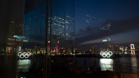 The Olympic rings are reflected in the glass wall of a wedding chapel in the Odaiba section of Tokyo, Monday, March 23, 2020. The Tokyo Olympics are going to happen — but almost surely in 2021 rather than in four months as planned. (AP Photo/Jae C. Hong)