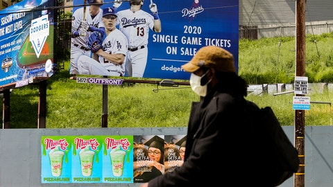 <p>               A pedestrian wears a hat and a face mask on Sunset Blvd., in the Echo Park neighborhood of Los Angeles, Thursday, April 2, 2020. Major League Baseball opening day was to have been Thursday, March 26, but was pushed back to mid-May at the earliest because of the coronavirus outbreak. The spring training schedule was cut short on March 12 because on the pandemic, and it remains unclear when and if baseball can resume. (AP Photo/Damian Dovarganes)             </p>
