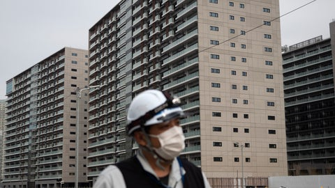 <p>               FILE - In this March 23, 2020, file photo, a worker walks through the athletes village for the Tokyo 2020 Olympics, in Tokyo. Tokyo's governor is considering the possibility of using the unfinished Olympic Athletes Village as a temporary hospital for coronavirus infected patients. The massive village on Tokyo Bay could house up to 18,000 people during the Olympics. (AP Photo/Jae C. Hong, File)             </p>
