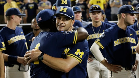 """<p>               FILE - In this June 26, 2019, file photo, Michigan coach Erik Bakich, center, is hugged by Michigan's Ako Thomas (4) as they watch Vanderbilt celebrate after Vanderbilt defeated Michigan to win Game 3 of the NCAA College World Series baseball finals in Omaha, Neb. As disappointing as it's been to have the college baseball season shut down because of the coronavirus pandemic, Michigan coach Erik Bakich sees a silver lining. """"I do think the coming years will be the deepest college baseball has ever been,"""" he said. (AP Photo/Nati Harnik, File)             </p>"""
