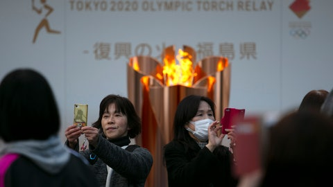 <p>               FILE - In this March 24, 2020, file photo, people take pictures with the Olympic Flame during a ceremony in Fukushima City, Japan. The Olympic flame has been removed from public display in Japan, and it's not clear when it will reappear again or where. The flame arrived in Japan from Greece on March 26. (AP Photo/Jae C. Hong, File)             </p>