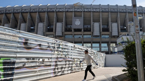 <p>               A woman wearing a protective mask walks past Real Madrid's Santiago Bernabeu stadium in Madrid, Spain, Friday, March 13, 2020. Real Madrid have said its players were being placed in isolation after one of the club's basketball players, who share facilities with Madrid's soccer players, tested positive for the COVID-19 coronavirus. That led to the instant decision by the Spanish league to bring matches to a halt for the next two rounds. For most people, the new coronavirus causes only mild or moderate symptoms. For some it can cause more severe illness, especially in older adults and people with existing health problems. (AP Photo/Paul White)             </p>