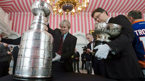 <p>               FILE - In this March 16, 2017, file photo, Phil Pritchard, left, picks up the Stanley Cup as Craig Campbell, right, holds the original Stanley Cup following an event commemorating the cup's 125th anniversary at Rideau Hall in Ottawa, Ontario. The NHL is on hold, the cup is locked up inside the Hockey Hall of Fame and longtime keeper Pritchard has shed his trademark white gloves to work from home like so many others during the coronavirus pandemic. (Adrian Wyld/The Canadian Press via AP, File)             </p>