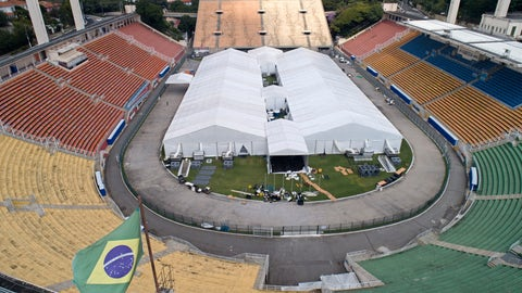 <p>               Workers set up a temporary field hospital to treat patients who have COVID-19 inside Pacaembu stadium in Sao Paulo, Brazil, Monday, March 30, 2020. (AP Photo/Andre Penner)             </p>